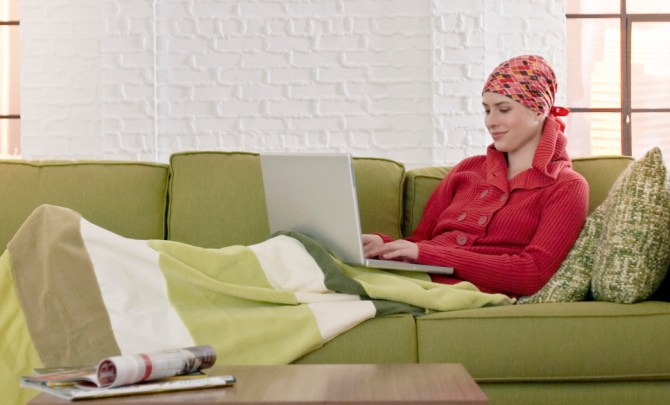 Young woman with cancer on laptop.