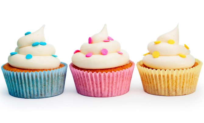 Beautiful cupcakes sitting on surface.