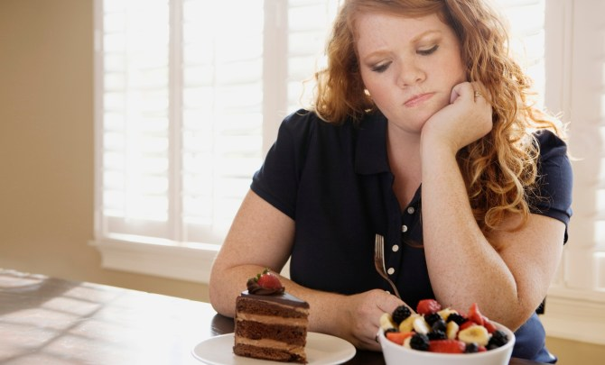 Overweight woman thinking about what to eat.