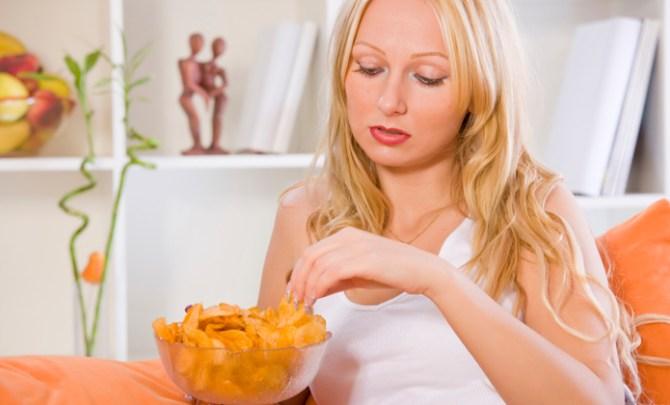 sad woman eating snacks at home