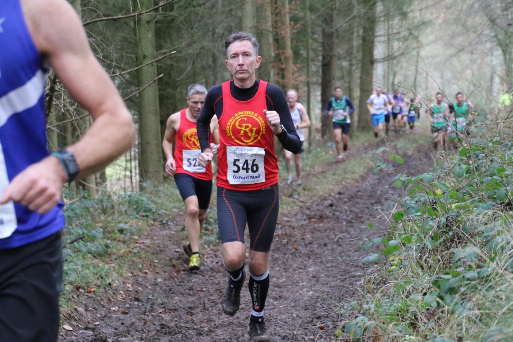Determined runner in the muddy woods at Cirencester Cross Country, 2nd lap | SpryUltra.uk | Simon Prytherch | Ultrarunner & coach