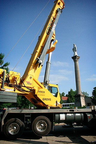 A large crane was used to transport the bronze statue.