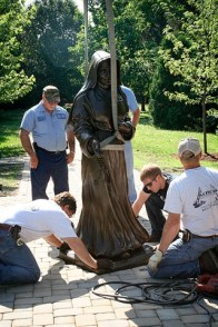 The workers measure to see if the statue is level.
