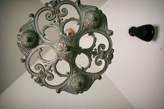 This beautiful metal light fixture hangs from the ceiling.