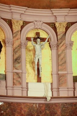 The crucifix is placed high above the altar.