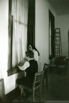 Sisters Mary Albertine Coppersmith and Clare Therese Bullock hanging curtains in the new Community Room at Providence Hall, a sisters' residence for the Sisters of Providence of Saint Mary-of-the-Woods, Indiana.