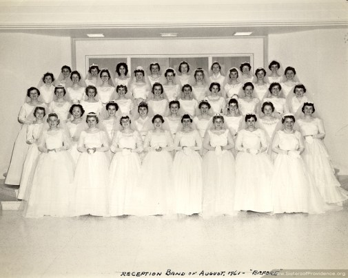 """The 44 postulants in the reception band (class) of 1961 gathered in the Owens Auditorium as """"Brides of Christ"""" prior to their being received into the novitiate at a Eucharistic Liturgy in the Church of the Immaculate Conception. Prior to 1964, young women who were entering the novitiate dressed in wedding dresses and received the holy habit during the liturgy of entrance."""