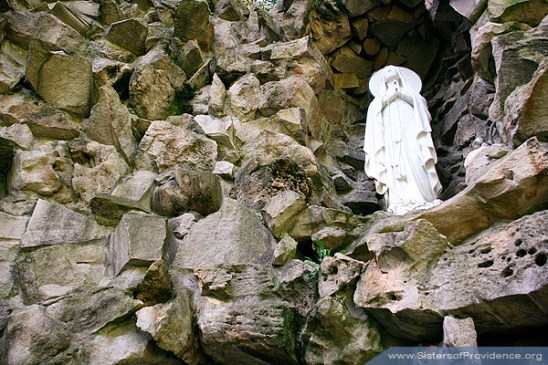 Mary sits above the grotto surrounded by craggy rocks.
