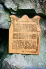 This wooden plaque explains the Grotto's history.