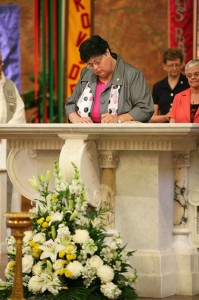 Sister Deborah Campbell signs her name, adding hers to the book that contains the names of thousands of Sisters of Providence who have gone before her, during her perpetual vows ceremony June 30 in the Church of the Immaculate Conception at Saint Mary-of-the-Woods.