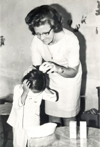 Sister Josephine during the Vietnam war treats a child in an orphanage for head lice.