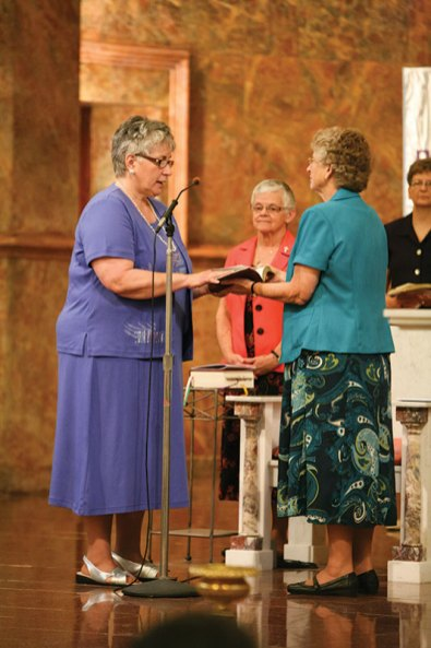 Sister Laura professes life-long vows as a Sister of Providence as Sisters Denise Wilkinson and Jenny Howard look on.