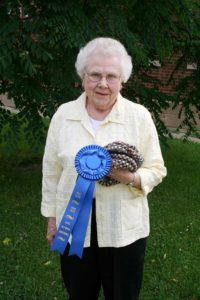 Sister Bernice with a ribbon she won in 2008 for knitting with alpaca fiber.