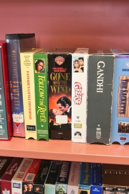 A small library nook has a full bookshelf of VHS tapes.