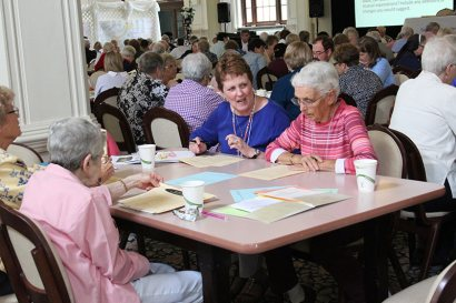 Providence Associate Assistant Director Debbie Dillow discusses business with Sisters of Providence at her table, including Sister Margaret Norris at right.