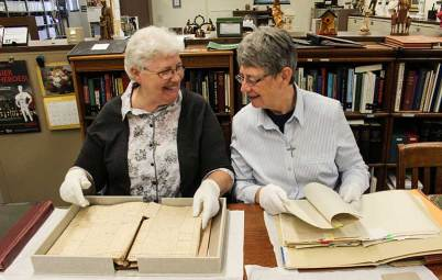 Sisters Martine and Henri Dominique in the Sisters of Providence Archives looking through Saint Mother Theodore's journals and letters.