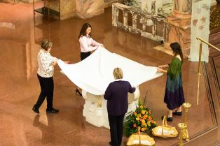 New Providence Associates, clockwise from left, Lorrie Scheidler, Tracy Biggs-Green, Amy Miranda and Suzie Ray prepare the altar cloth during Mass.