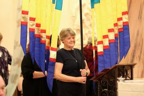 Sister Jody O'Neil prepares to carry a banner in during the liturgy's procession.