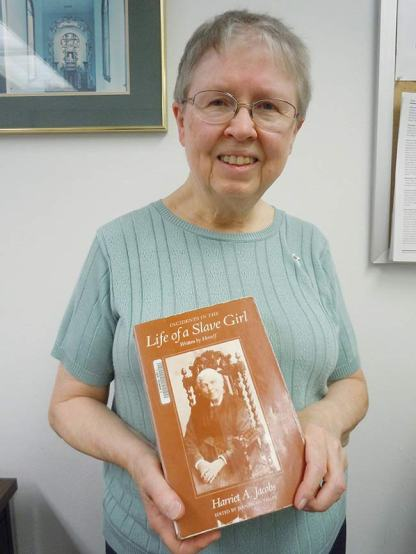 """Sister Donna Butler holding the book, """"Incidents in the Life of a Slave Girl,"""" written by Harriet Jacobs."""