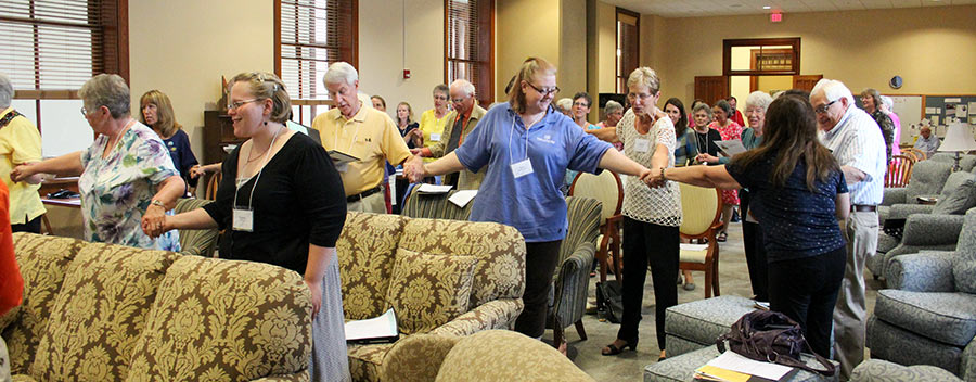 Providence Associates join hands in prayer during a gathering.