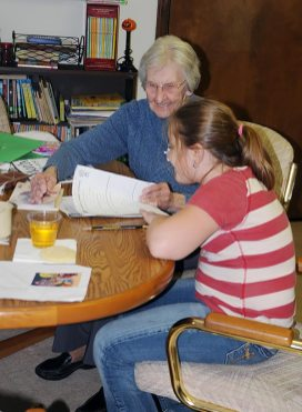 Sister Mary Ann Lechner volunteers helping a girl with her homework at EFS in 2012.