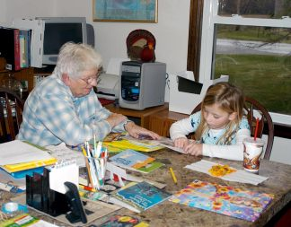 Sister Mary Pat Peacock (RIP) helps a little girl with her reading in 2011.