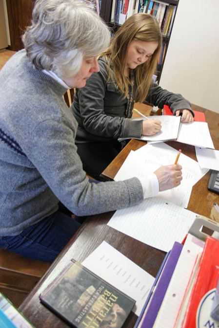 A volunteer tutors a student after school in 2012.