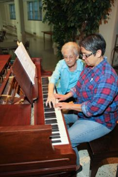 Sister Regina Marie McIntyre instructs Sister Joni Luna on the piano.