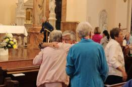 Sister Denise Wilkinson hugs Sister Rita Clare Gerardot during the sign of peace at the concluding Mass. (photo by Jason Moon)