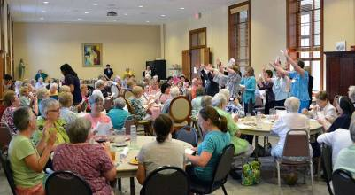 Providence Associates lead a lively song and dance during the supper social with the sistesrs. (photo by Amy Miranda)