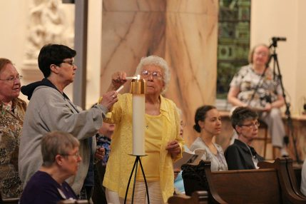 Sisters Carole Kimes and Mary Frances Keusal light their candles as chapter delegates during the opening ritual. (photo by Amy Miranda)