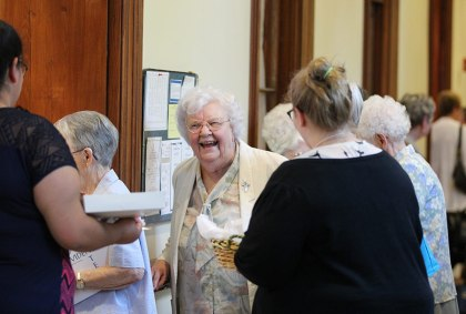 Providence Associates greet sisters and associates as they arrive at an evening meal social time for sisters and associates. Here Sister Mary Maxine Teipen speaks with Providence Associates. (photo by Amy Miranda)