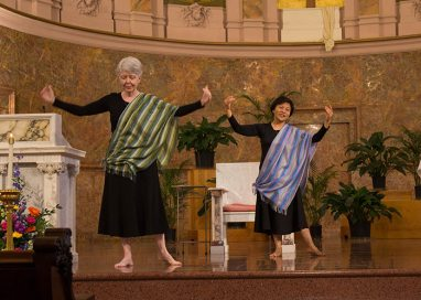 Sister Marsha Speth and Sister Editha Ben perform liturgical dance during the preparation of the altar for Mass