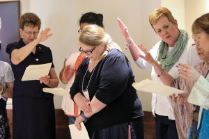 Providence Associate Kaitlyn Willy, who is currently in graduate school in Texas, renewed her commitment as a Providence Associate while at Saint Mary-of-the-Woods for Chapter. Here Sister Dawn Tomaszewski at left and Providence Associate Debbie Dillow at right, join with other sisters and associates to pray a blessing over Kaitlyn during her recommitment.
