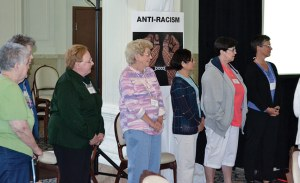 Sisters and associates choose justice issues they would like to focus on by moving to its sign in the room. From left, Sisters Mary Beth Klingel, Lucy Nolan, My Huong Pham, Carole Kimes and Providence Associate Maria Price show support for work to promote anti-racism.
