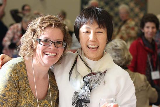 New Providence Associate Amy Langham, left, meets up with her college friend Sister Anji Fan at the reception.