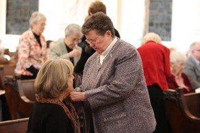 Sister Therese Whitsett pins the Providence Associate pin on her Providence Associate companion Joyce Smith.