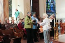 Karen Sue Goehl and Sandra Wickware bring up the gifts during the ceremony.