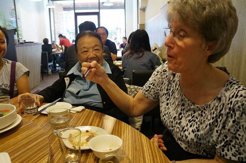 Sister Donna Marie Fu showing Sister Jeanne Hagelskamp how to use chopsticks.