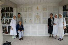 Sister Jeanne along with Sister Delan Ma and Sister Donna Marie Fu and other Missionary Sisters of Providence during a visit to the graves of Mother Marie Gratia Luking and Sister Regina Marie Wallace.
