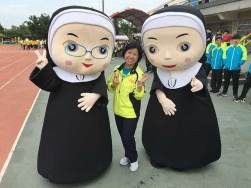 """Sister Norene Wu with characters """"Peace and Joy,"""" mascots for the 60th anniversary."""