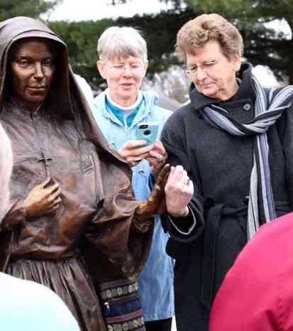 Sister Mary Montgomery (center) takes a photo of General Superior Sister Dawn Tomaszewski, venerating the statue of Mother Theodore. Notice that both are wearing their Saint Mary-of-the-Woods College rings, bringing to mind the first academy started in Indiana by Mother Theodore.