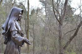 Saint Mother Theodore Guerin statue against the backdrop of the log cabin chapel, the first place that Mother Theodore and her companions visited when arriving at Saint Mary-of-the-Woods in 1840.