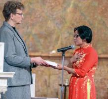 Sister Dawn holds the Bible as Sister My Huong makes her vows as a Sister of Providence on Feb. 25.
