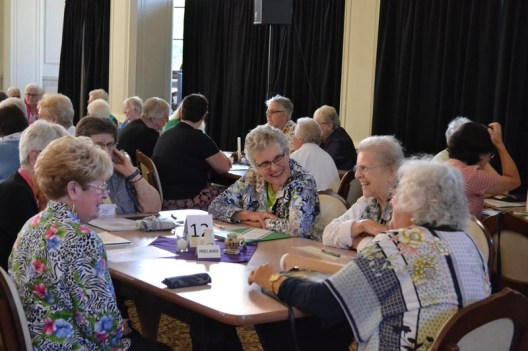 Sisters Mary Moloney and Marie Grace Molloy laugh with others at their table during the annual meeting days with associates.