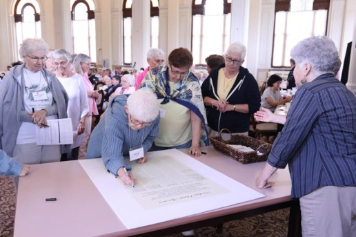 Signing the Providence Climate Agreement, from left, are Sisters Mary Catherine Guiler, Florence Norton, Maria Saracco and Cynthia Lynge.