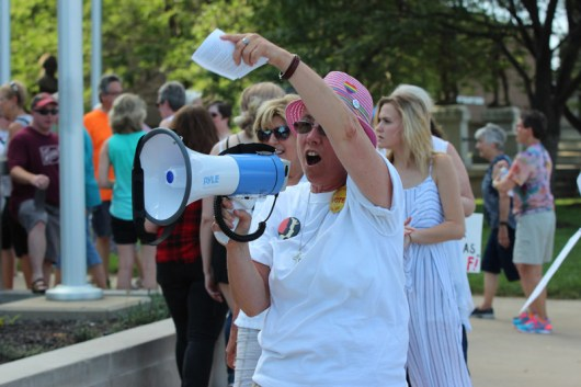 Some sisters and associates joined a peaceful protest to keep immigrant families together at the Vigo County courthouse Saturday evening. Here Sister Barbara Battista helps gather people in.