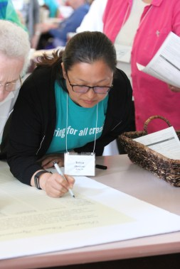 Postulant Teresa Kang signs the Providence climate agreement.