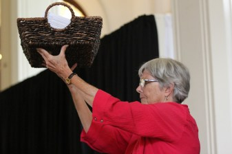 Sister Barbara Sheehan holds up the basket of Providence Climate Agreement forms filled out by sisters and associates.