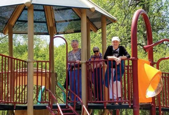Sisters Teresa Costello, Suzanne Buthod and Ann Stephen Stouffer atop the playground equipment at Deming Park
